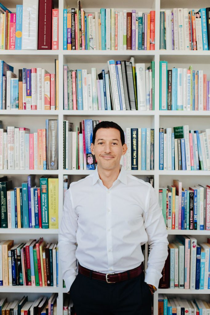 Dr. Cabral Standing at his book shelf
